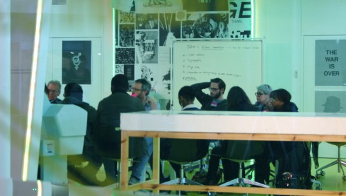 A group of people sitting round a table - photo taken through a green tinged window